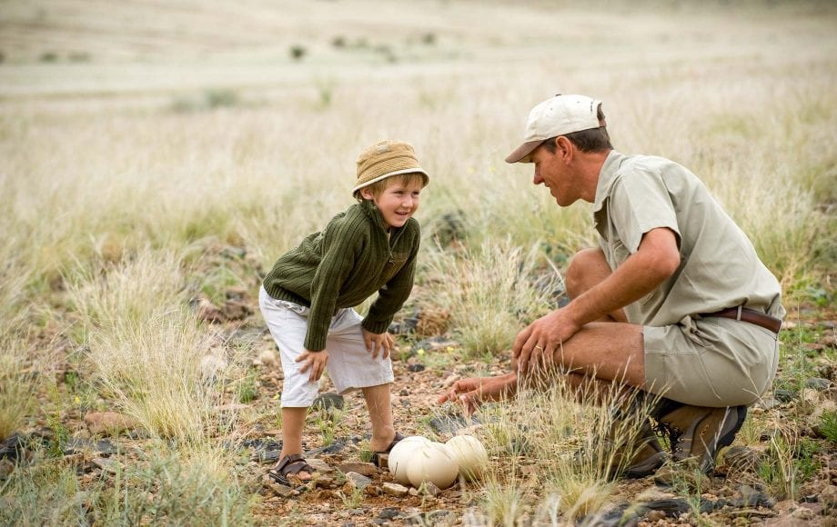 Curious boy happily chatting with a man at Sossusvlei Namib Desert