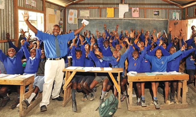 Happy students and teacher in a school in Africa